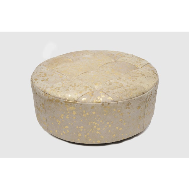 This round floating ottoman is upholstered in a dazzling metallic etched Brazilian hair-on-hide in shades of white & gold....