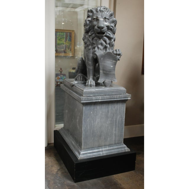A pair of Italian carved marble lions on pedestals, formerly the property of a wealthy East Javanese sugar baron who...