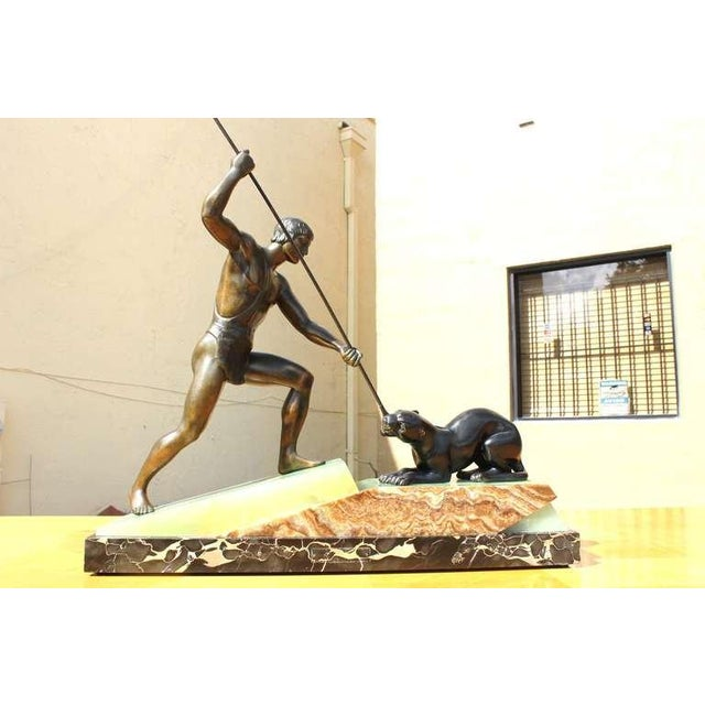 A French Art Deco Patinated Metal Sculpture of a Hunter Taming a Tiger signed Lemoine, on Marble Base.