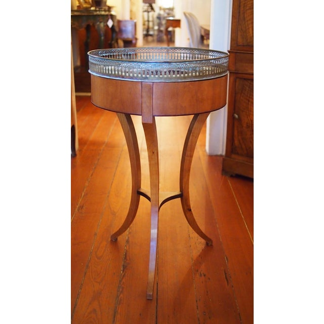 A veneered plant stand with three sinuous legs joined by a stretcher, the walnut veneer accented with an ebonized inlay...