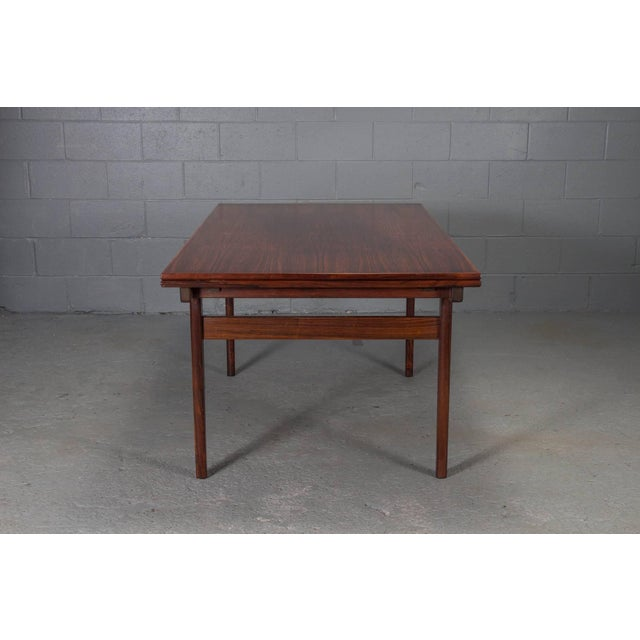This modern Danish dining table is made of rosewood by Vejle Stolefabrik. It extends to accommodate larger parties and...