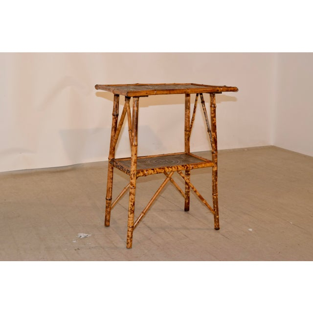 19th century French tortoise bamboo table with splayed legs joined by a lower shelf. The top and lower shelf are both...