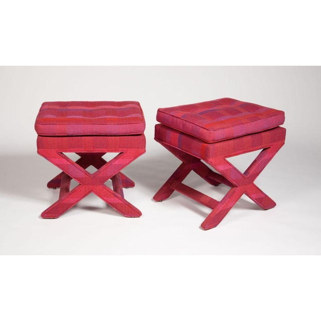 A pair of benches with fully upholstered x-frame bases. The upholstery is original Larsen fabric in a sumptuous fuchsia...