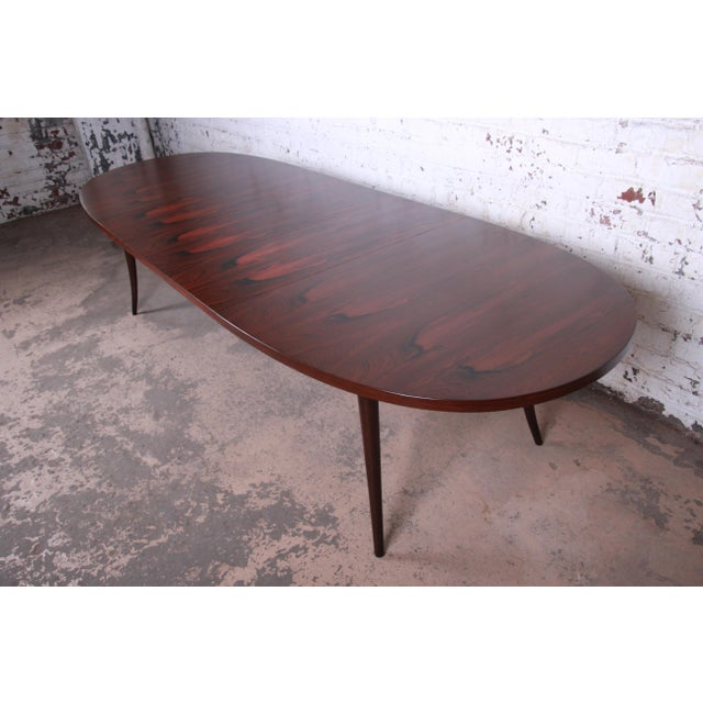 A rare and exceptional saber leg rosewood extension dining table Designed by Harvey Probber USA, 1950s Book-matched...