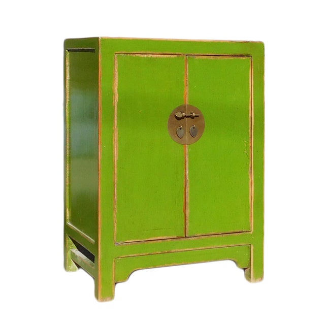 This is a simple mid-size end table nightstand with rustic lime green lacquer finish. It is decorated with round moon face...
