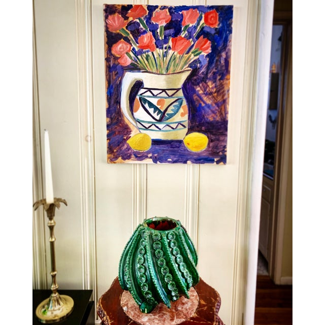 Bold alive farmhouse style still life of a bursting bouquet of crimson flowers in a large rustic pitcher. Abstract blue...