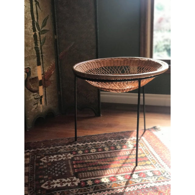 Offering a rattan and wrought iron catch all basket. The basket sits in between a round wrought iron piece with 3 legs....