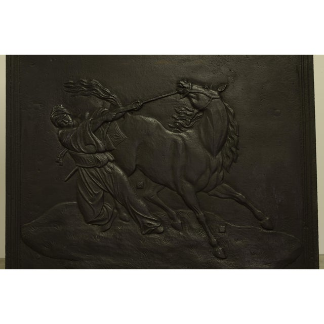 Nice square antique cast iron fireback showing a man trying to tame a wild horse. Perfect square dimensions, excellent...