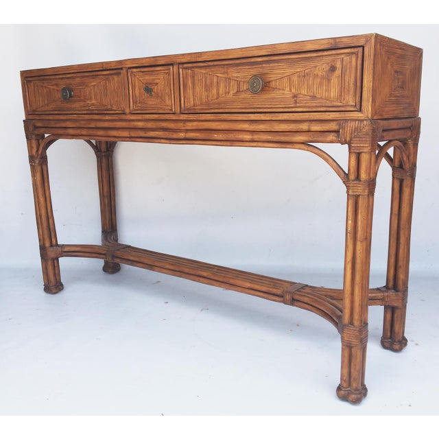 Three drawer console features sturdy rattan construction framed in reeded bamboo and rawhide lacing. Burnt wood treatment...