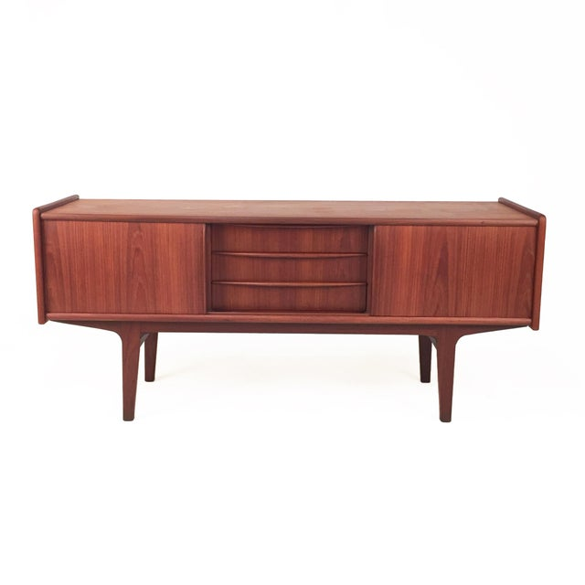 A teak sideboard brimming with charm and character, this mid-century modern storage piece features beautifully tapered...
