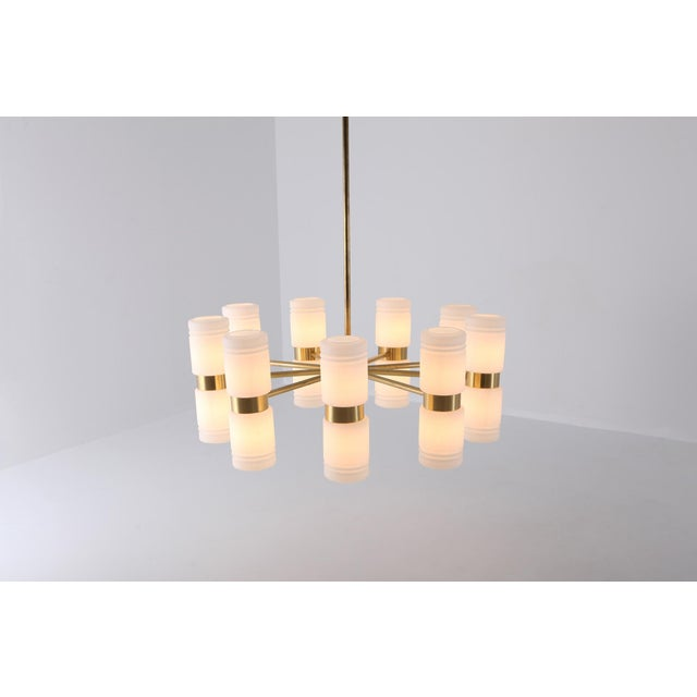 Midcentury Scandinavian Modern chandelier by Hans-Agne Jakobsson in brass and milky white opaline glass shades. Huge and...
