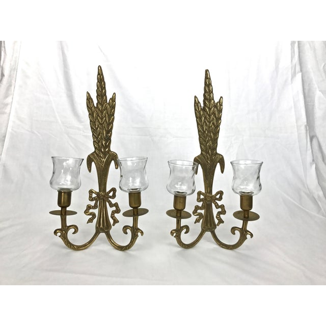 Set of two Hollywood Regency ornate brass candle sconces with removable glass votive holders. Hanging hardware attached....