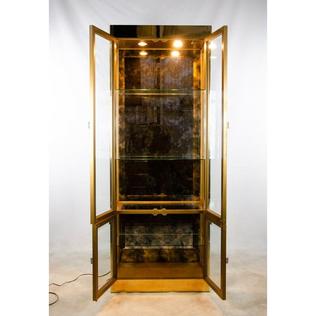 Bring the glitz and glamor to any room with this stunning brass clad display cabinet made by Mastercraft. The brass frame...