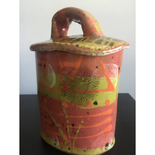 Unique and colorful pottery vessel with handle lid. Lime green, salmon pink and orange are glazed all over this piece....