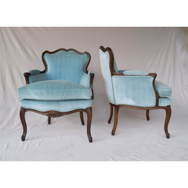 A pair of mid 20th century French Provincial carved Berger'e chairs. Original finish features well maintained blue velvet...