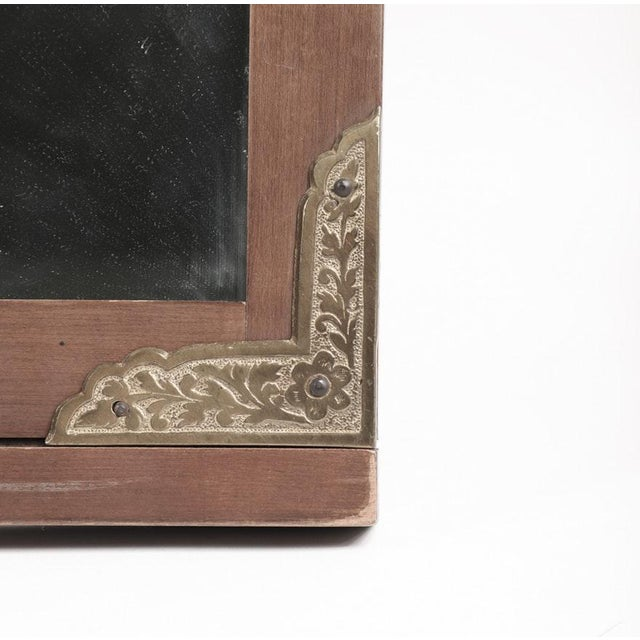 A Drexel wall mirror. This mirror features a cherry wood frame fitted with brass accents at each corner. It is marked...