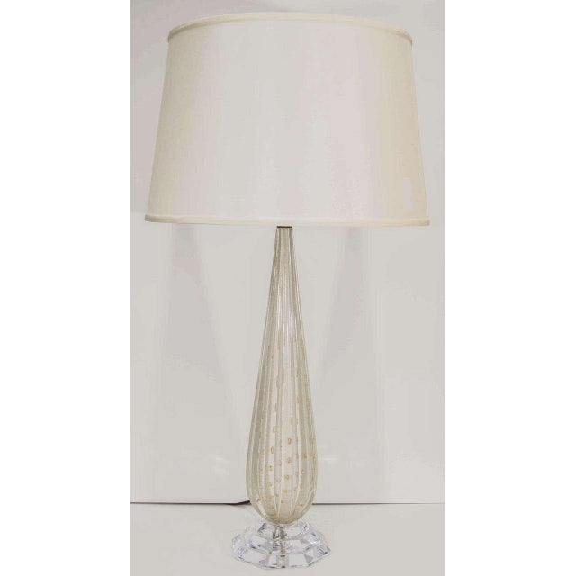 A glamorous fluted lamp in Murano glass with gold leaf inclusions on a Lucite base.