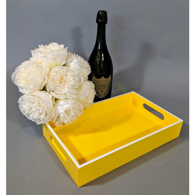 This bright yellow and white trimmed lacquered tray is classy but understated at the same time. Trimmed on the interior...