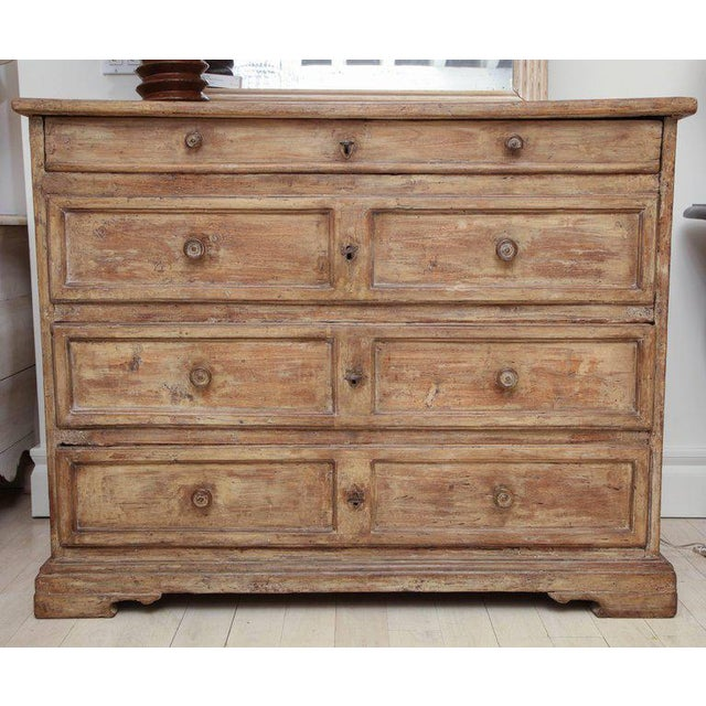 Antique poplar commode with four paneled drawers, original walnut pulls and bracket feet. *This commode is available to...