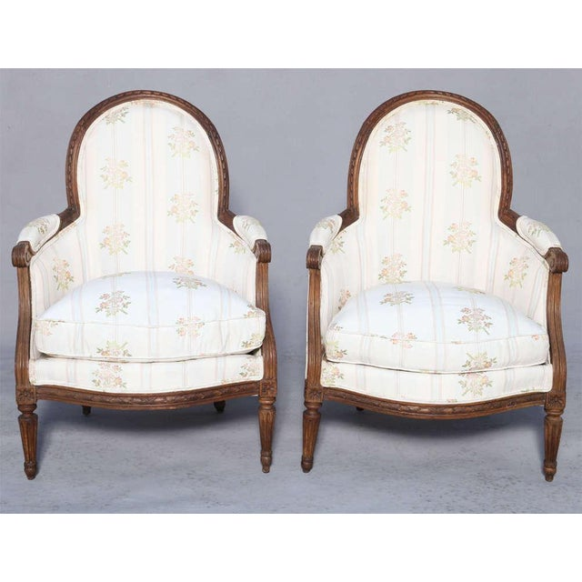 An important pair of period child's bergère chairs, of walnut; each oval padded backrest in gadrooned frame, outswept...
