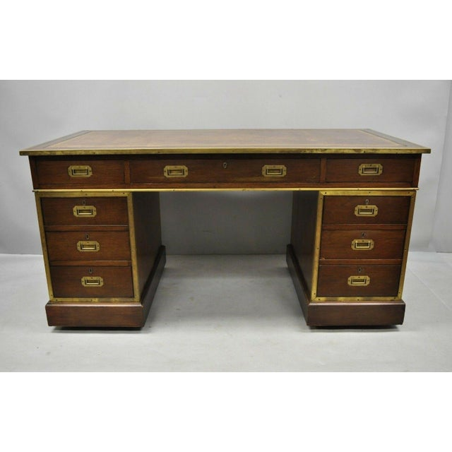 Antique mahogany English campaign pedestal desk with brown tooled leather top. Item features brown tooled leather top,...