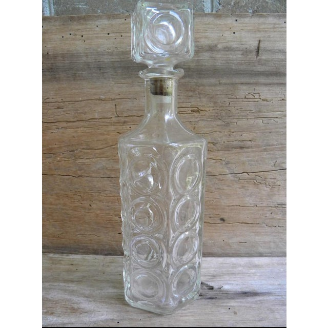This vintage mid century liquor decanter is made of clear glass with a beautiful, unique circular pattern. Bottle is...