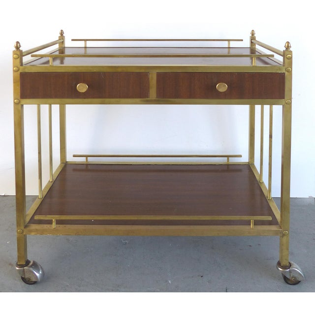 Offered for sale is a vintage brass rolling bar trolley or bar cart. The brass is in good vintage condition with expected...
