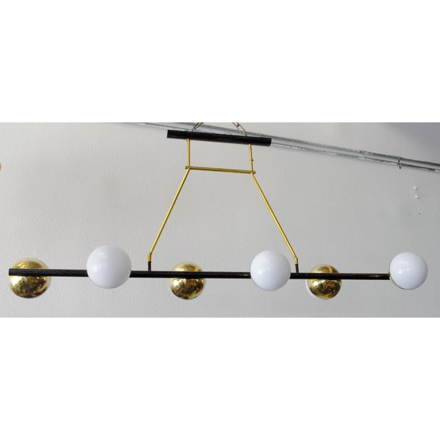 Modern Italian chandelier shown with six glossy white Murano glass globes and polished brass frame, designed by Fabio...
