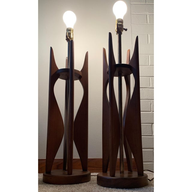 Item: For your consideration we are presenting for sale a pair of handsome vintage sculptural rocket-style walnut table...