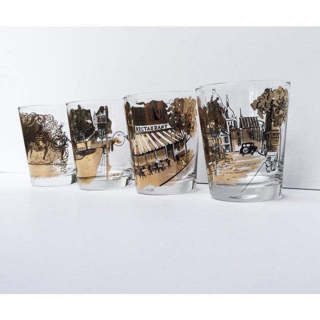 A great set of four vintage French scene black and gold bar glasses! These midcentury drinking glasses are slightly...