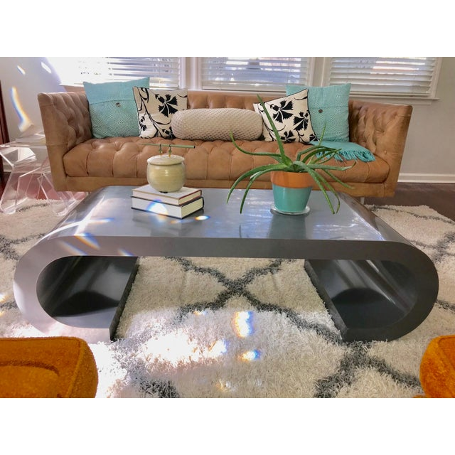 This grey scroll coffee/cocktail table is in the style of luxury designer Karl Springer, Circa 1970's. The table suits a...
