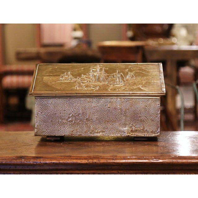 Crafted in France, circa 1920, the antique wood and brass coffer stands on wooden feet, the slant top opens up and reveals...