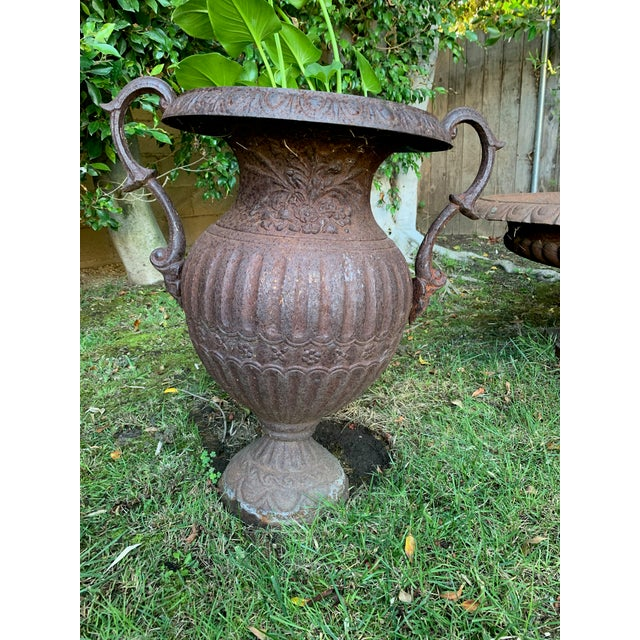 Antique Distressed Iron Urn with decorative handles. Perfect as a stand alone accent piece for your garden or as a planter.