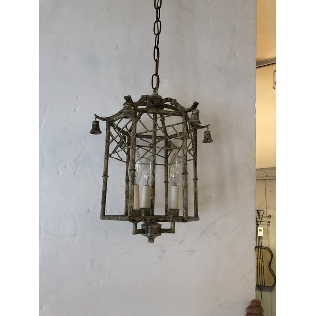 A medium sized stylish faux bamboo pagoda style lantern chandelier having faux painted iron and tole in a neutral chic...