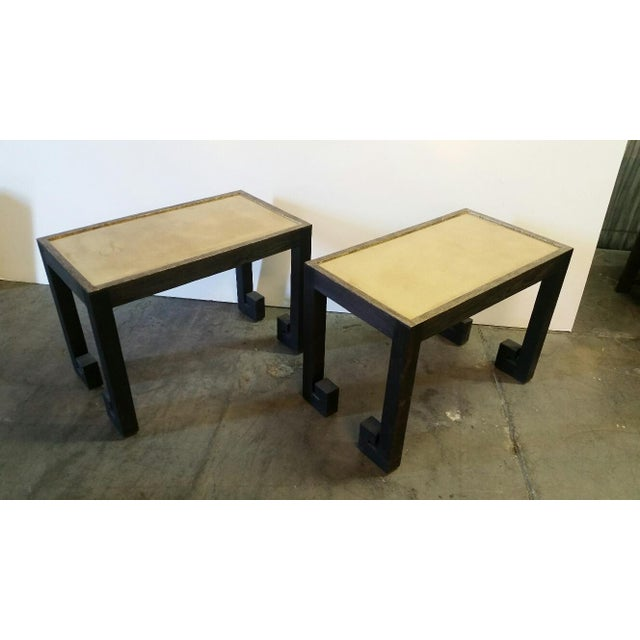 Pair of Greek Key Tables by Paul Marra in distressed wood with black finish and top edges in mottled gold. Casual...