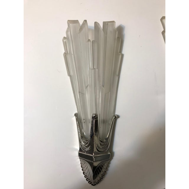 Pair of French Art Deco sconces by G Leleu. Having clear frosted glass shades with geometric motif details throughout....