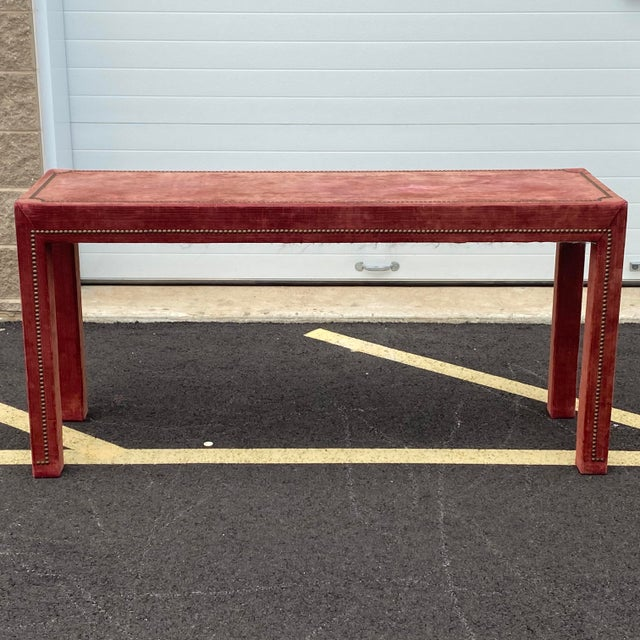 A unique parsons style upholstered console table with distressed red velvet and brass nailhead details.