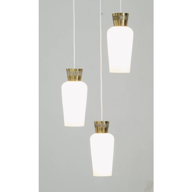 A 1950s chandelier from Finland, in the manner of Paavo Tynell and Lisa Johansson-Pape. The lamp is made of a three...