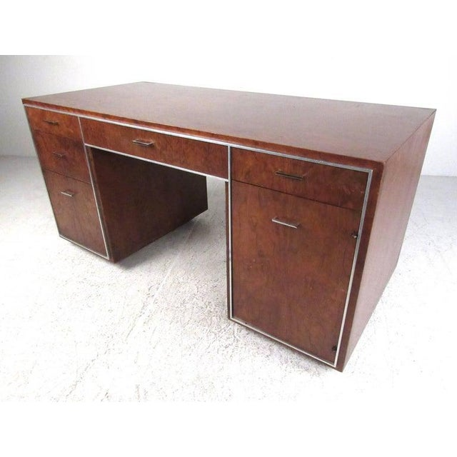 Attractive deep grain patterned walnut desk with simple lines accentuated by aluminum trim and matching drawer pulls....