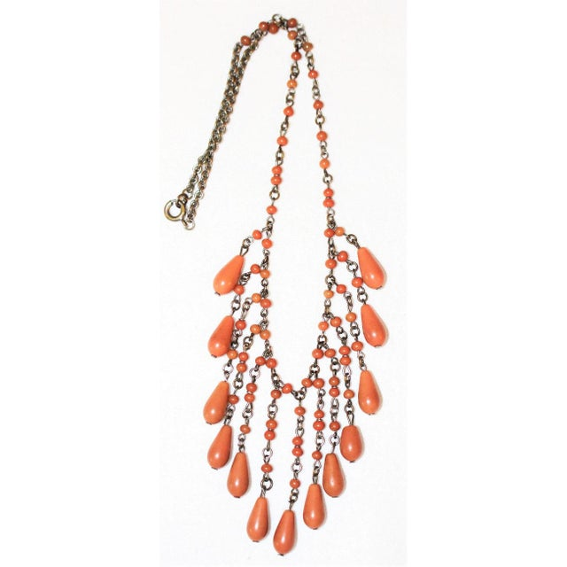 Circa 1920's Art Deco era coral-color celluloid bead and drop bib necklace made on fine brass link chain. The necklace...