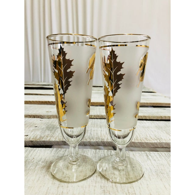 A set of two vintage frosted gold leaf pilsner glasses. Some of the gold detailing and rim has begun to wear off as can be...