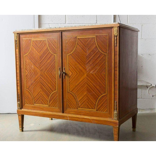Small French buffet with inlayed marquetry doors, original brass hardware and green marble top. Late 19th or early 20th...