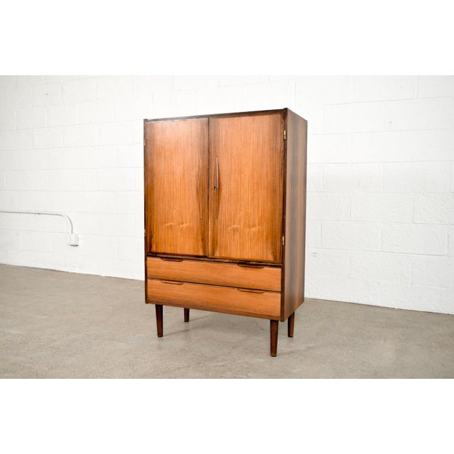 This striking vintage mid century Danish modern bar cabinet in the manner of Arne Vodder or Finn Juhl and circa 1960 is...