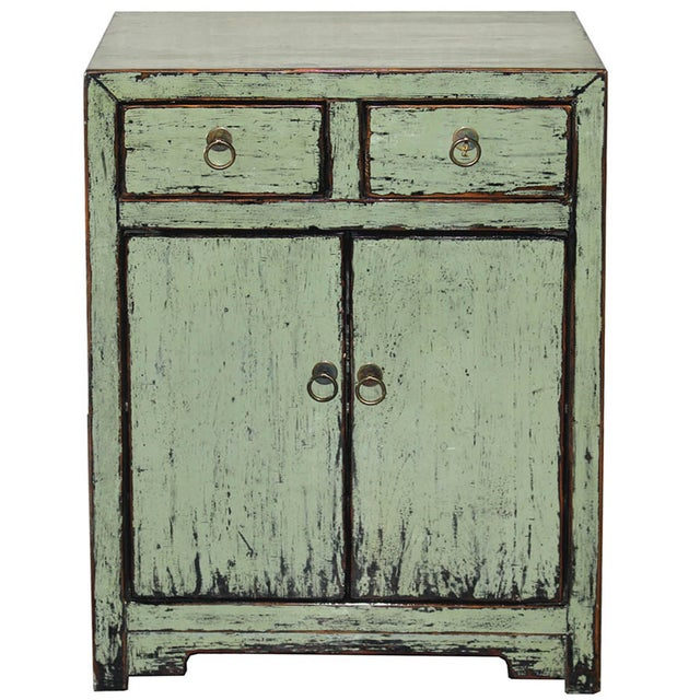 A distressed, sage-green, lacquered, two-drawer elm wood side chest with exposed wood edges. This piece will sit perfectly...