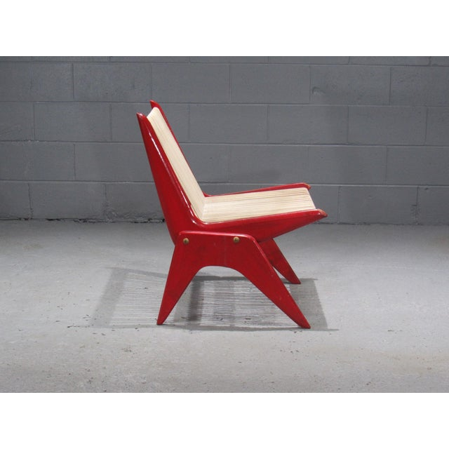 Red painted wood and rope scissor chair.