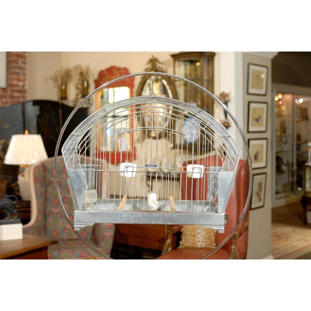 20th century American chrome plated bird cage suspended from a hoop floor stand. The bird cage was made by Hendryx during...