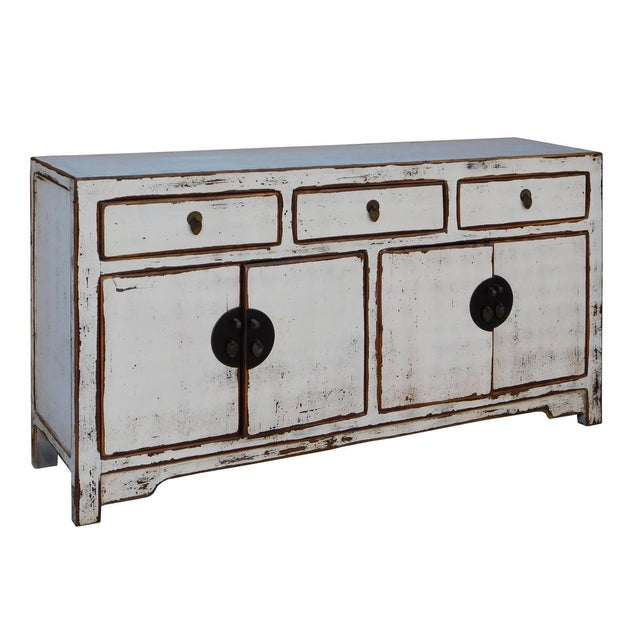 This is a sideboard cabinet table with four drawers and two compartments. It is finished with rustic distressed off White...