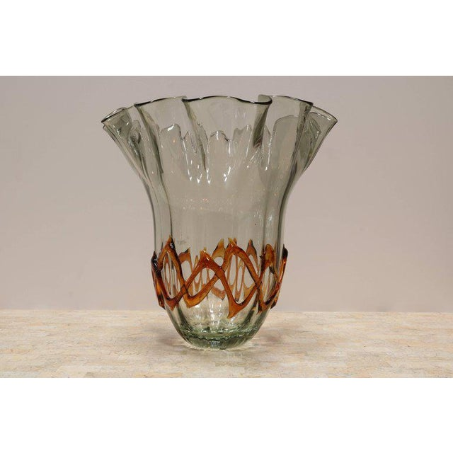 Fluted glass vase has a handkerchief edge and ribbons of amber colored glass around the bottom.