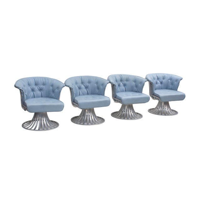 Set of four aluminum tulip chairs by Woodard. The frames are quite curvy; flat ribbons of aluminum create a classic tulip...