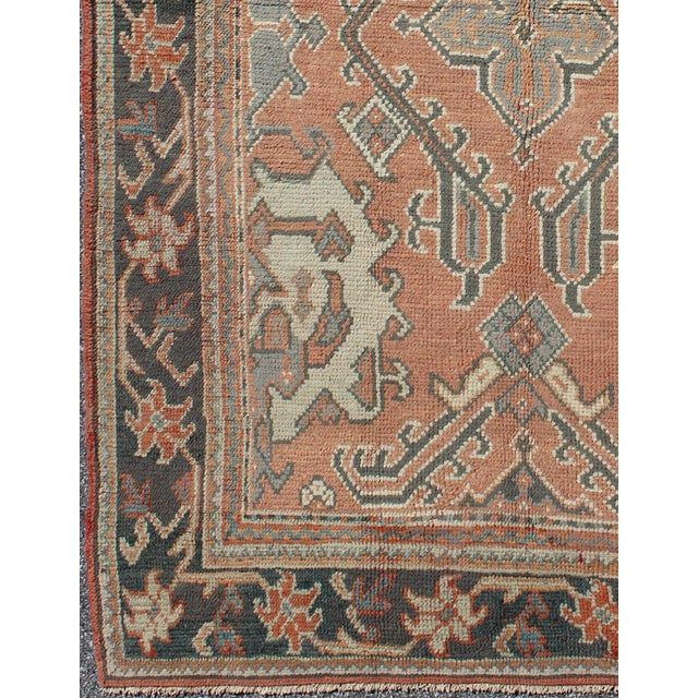 This antique Turkish Oushak carpet features a central medallion design, as well as patterns of smaller sub-geometric...